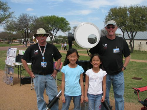 Cherry and Coco stand with astronomy enthusiasts and their telescope.